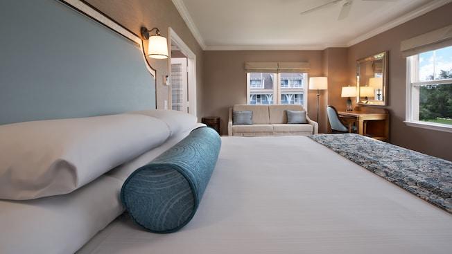 Un almohadón decorativo en forma de tubo delante de 4almohadas en una cama King Size