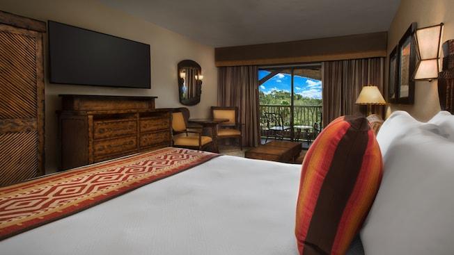 Una cama con almohadones decorativos, un armario y una cómoda, un TV de pantalla plana y una mesa con 2sillas