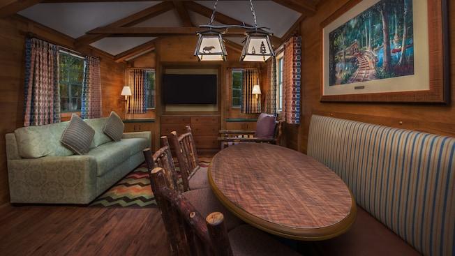 Una mesa de comedor rústica en frente de una silla, un sofá con almohadones decorativos y un TV de pantalla plana
