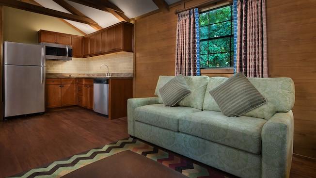 Un sofá al lado de una cocina abierta con un refrigerador de tamaño completo, microondas, lavavajillas y fregadero