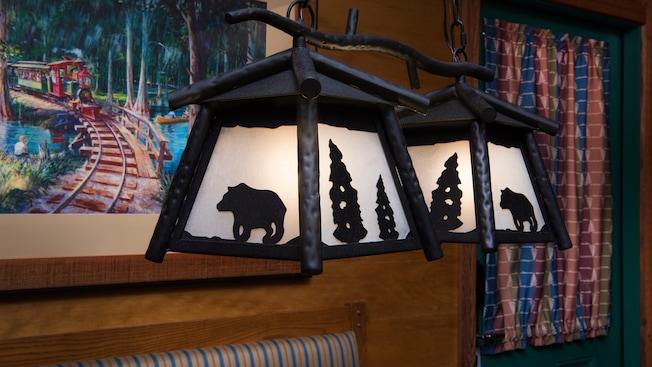 Un aplique de luz colgante con siluetas de metal rústico de pinos y osos