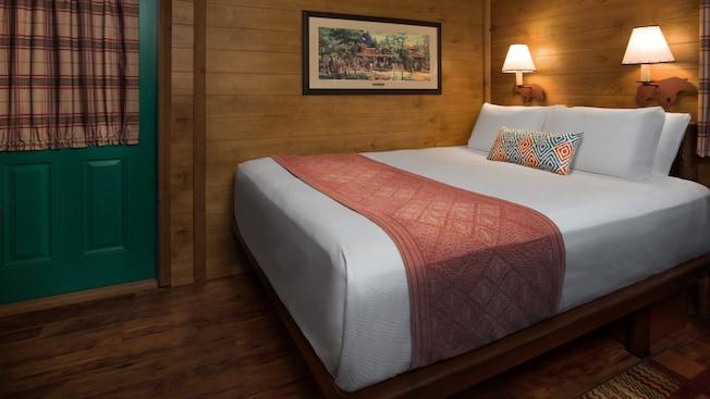 Una puerta al lado de una cama Queen Size con un cubrecama