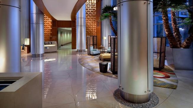 Pilares de acero,, pisos de azulejos blancos y palmeras en macetas en el lobby de Bay Lake Tower