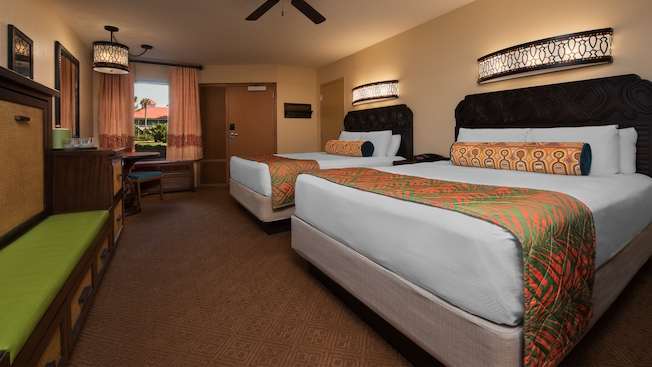 Dos camas Queen Size de estilo caribeño, asiento para equipaje/cama nido, mesa redonda y, detrás, una puerta y una ventana
