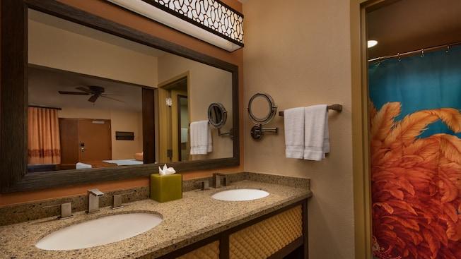 Un gran espejo rectangular sobre una encimera con doble lavamanos