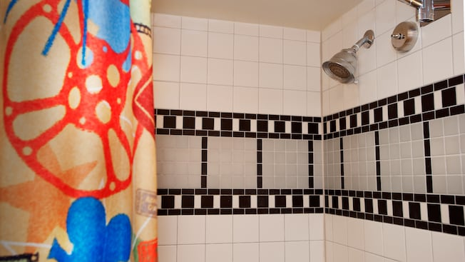 Shower with film strip design and curtain featuring cinematic designs