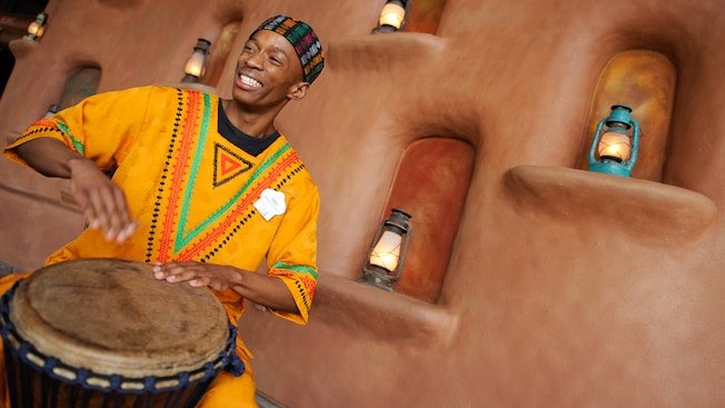 A man in traditional African garb plays a hand drum
