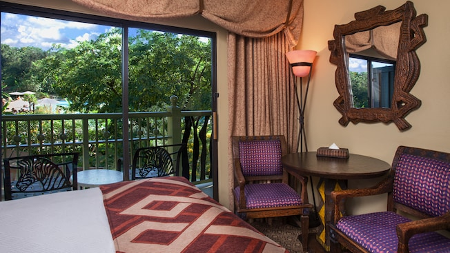 Pedestal table, cushioned chairs, wall mirror, bed, curtained private balcony with pool view