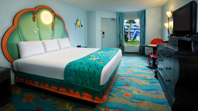 A king bed with an underwater theme across from a TV-dresser and, detrás, una puerta y una ventana
