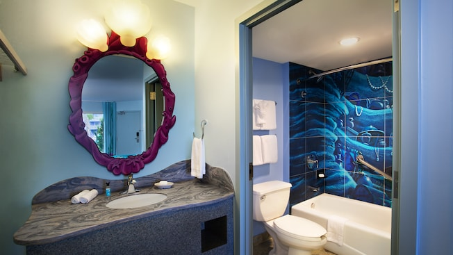 An oval mirror above a bathroom sink next to a room with a toilet and a bathtub-shower