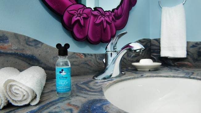 Two rolled-up washcloths and a complimentary shampoo bottle next to a bathroom sink