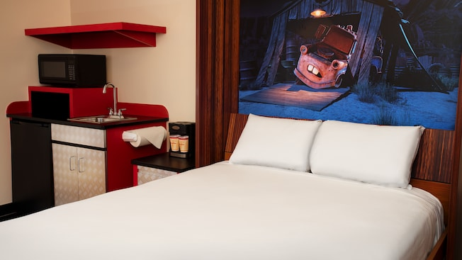 A Murphy-style double bed with a picture of Mater above it next to a kitchenette
