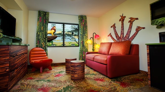 A living area with a double sleeper sofa, a wall decoration of giraffes, a TV-dresser, chair and window