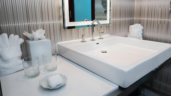 Una encimera pequeña con artículos de tocador junto a un lavamanos y un espejo arriba
