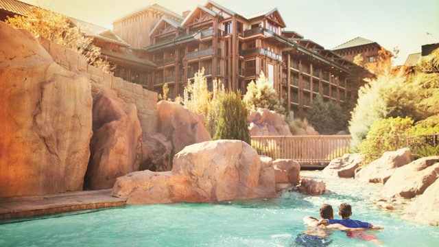 Un padre y su hijo nadan tomados del brazo en la piscina Copper Creek Springs