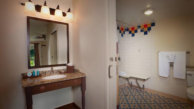 Un espejo sobre el lavamanos del baño junto a una habitación con una ducha adaptada para silla de ruedas