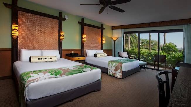 Two queen beds with rattan headboards next to an easy chair and, detrás, un patio y jardín