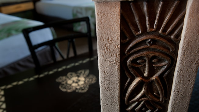 A lamp base with a tiki god-like design on a desk and, detrás, a chair and 2 queen beds