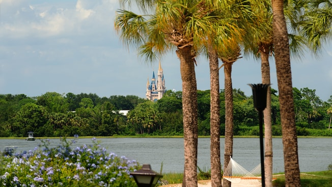 A hammock in a grove of 5 palm trees and, beyond, Seven Seas Lagoon and Cinderella Castle