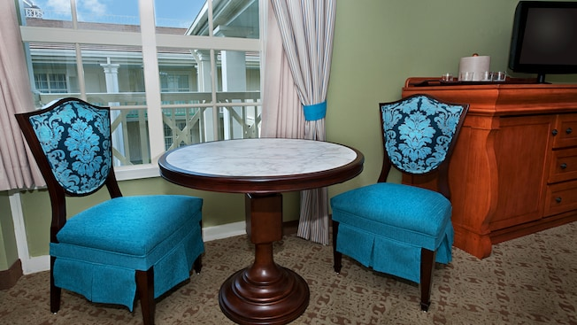 Round marble top side table, brocade chairs and dresser near curtained window with balcony view