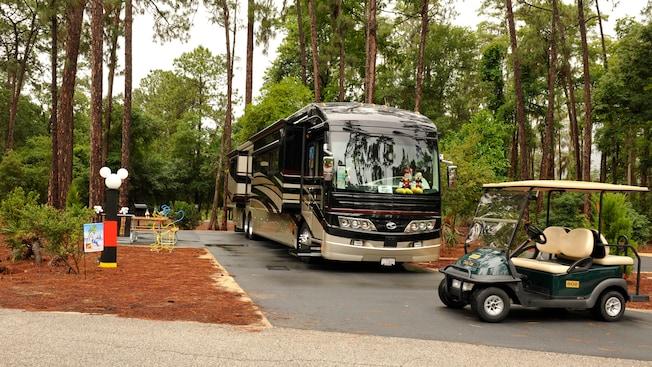 Carrito de golf aparcado delante de un autobús reluciente estacionado en un sitio arbolado