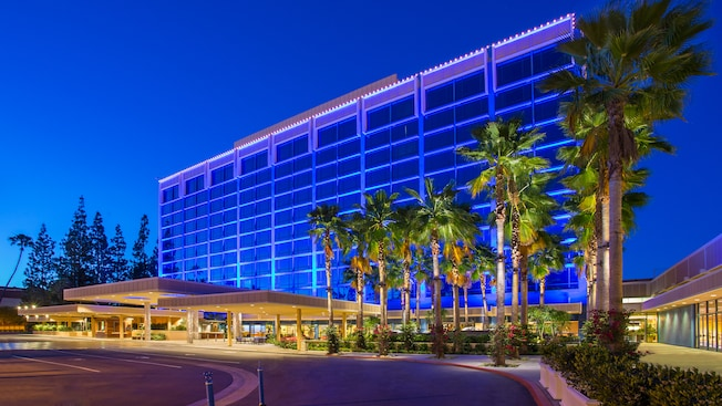 At dusk, the main Disneyland Hotel building rises above a valet parking area lined with palm trees