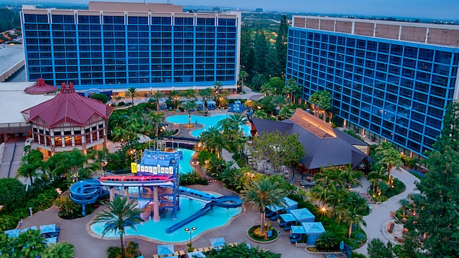Disneyland Hotel towers rise over a waterslide, swimming pools and gardens at sunset