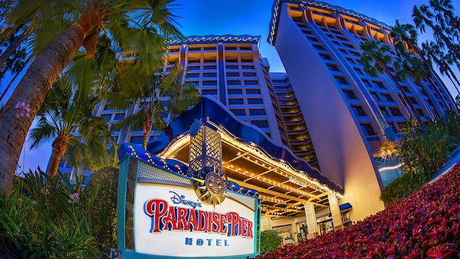 Hotel towers surrounded by palm trees and gardens with a brightly lit marquee sign at the hotel entrance