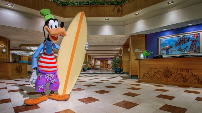 Disneys Goofy, dressed in outmoded beach wear, holds a surfboard at his side in a hotel lobby