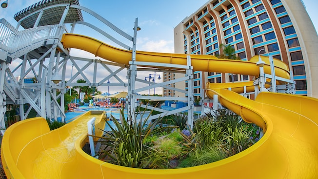 A twisting waterslide with launch platform in front of a hotel pool and tower, accented by lush gardens