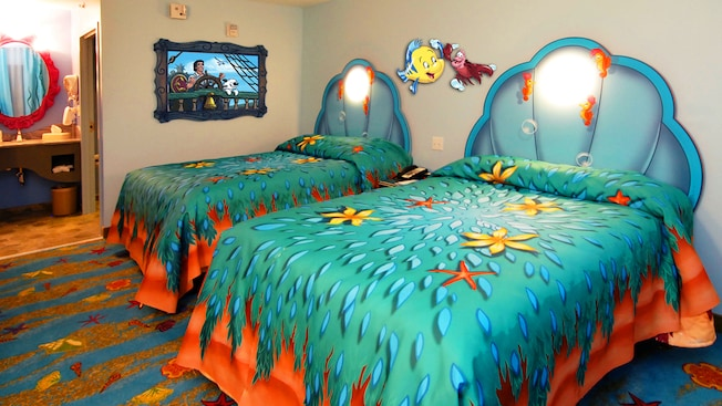 2 double beds in a Little Mermaid-themed bedroom next to an alcove with a vanity