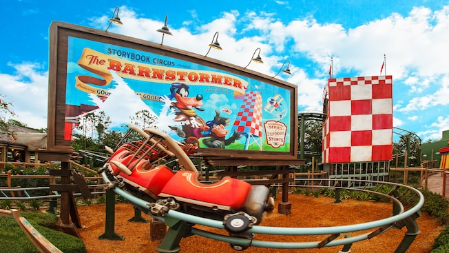 A junior rollercoaster speeds past a billboard for The Barnstormer featuring the Great Goofini