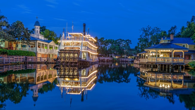 A nighttime view of the 3-tiered riverboat Liberty Belle docked at Liberty Square Riverboat Landing
