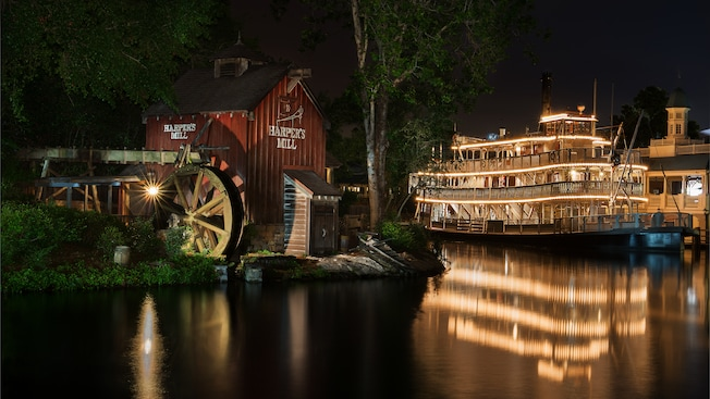 Harper's Mill on Tom Sawyer Island sitting across from Liberty Square Riverboat at night