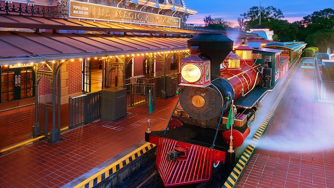 A steam-powered train waiting at Walt Disney World Railroad - Main Street, U.S.A. station at night