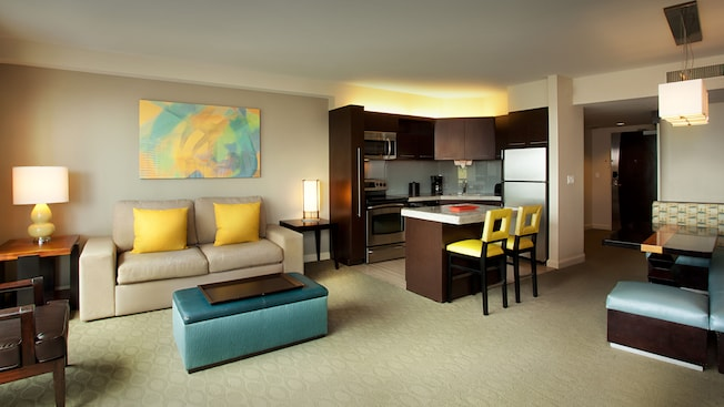 Living area with sofa, ottoman, arm chair, and end tables in an open layout to the kitchen and dining areas