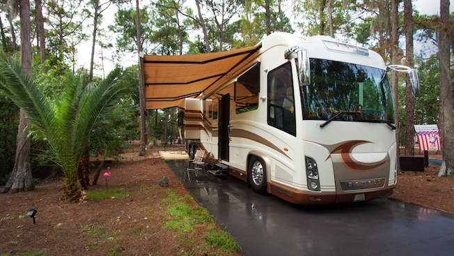 An RV with awning parked on a cement pad in a campsite after a rain
