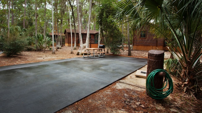 Campsite's concrete parking pad with water-hose hook-up on one side and a charcoal grill and picnic table on the far side