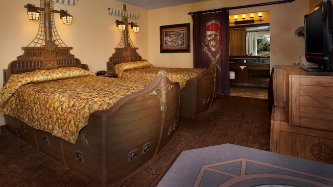 Pirate-themed room with ship-inspired headboard opposite a flat-screen TV