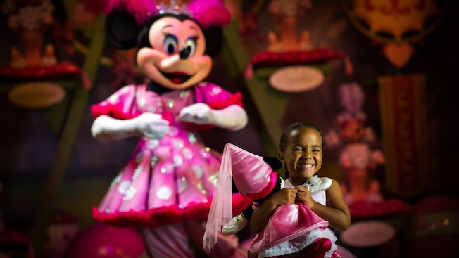 A delighted young girl holds a Minnie Mouse doll tightly while Minnie stands behind her