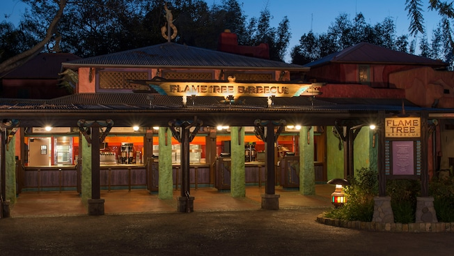 The Flame Tree Barbecue housed in a traditional African style building with an outdoor service area, consisting of a patio sheltered by a corrugated tin roof, a sign with the restaurant name on top of the roof and a menu board located to the right side as you approach