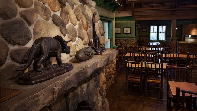 stone fireplace with dinosaur statues on mantle next to tables and