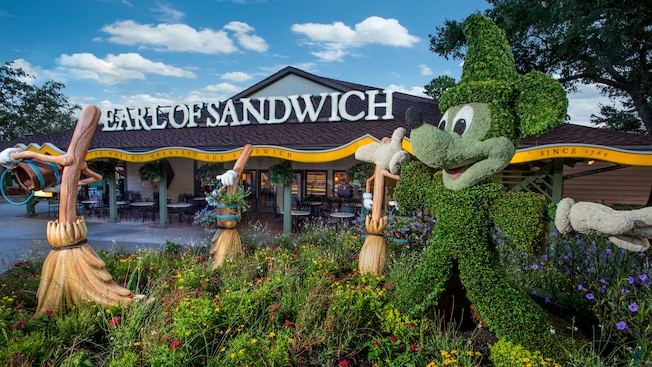 Enchanted brooms and topiary of Sorcerer Mickey outside Earl of Sandwich