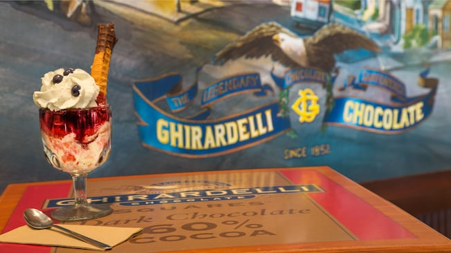 Haight AshBerry strawberry, vanilla and blueberry sundae on a table in front of Ghirardelli mural