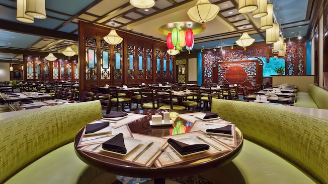 Round banquette booth for 6 in dining room with Asian lanterns and decorative wood panels