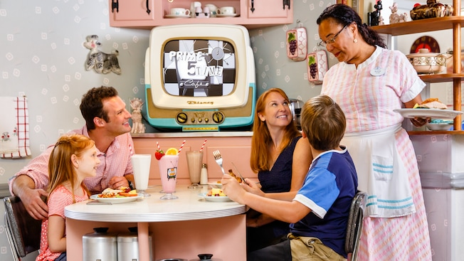 A Cast Member serves lunch to a family at 50's Prime Time Café