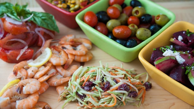 Shrimp, coleslaw and tomatoes in front of 3 containers holding olives, beets and corn