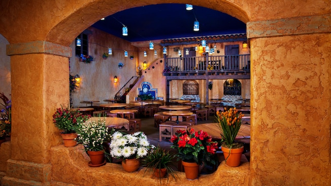 View of Southwestern dining area through an arched window with flower pots on its ledge