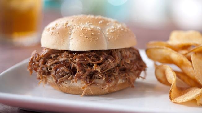 Un sabroso sándwich de cerdo desmenuzado en un panecillo con semillas de sésamo y servido con guarnición de papas fritas