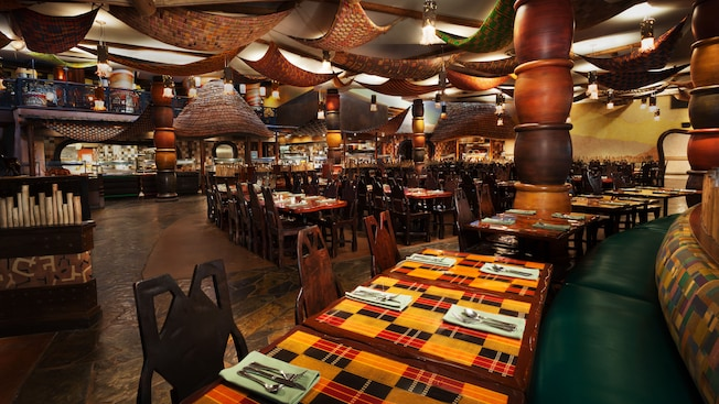 A dining section at Boma—Flavors of Africa restaurant with buffet stations in the background